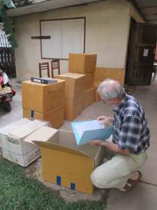 Ron looking through boxes of documents (from MCC Laos post on Ron and Sally Jo's blog)